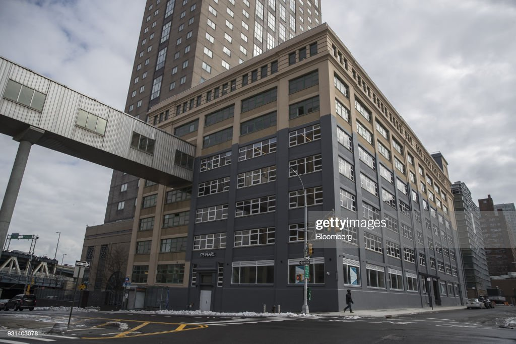A pedestrian walks past the 175 Pearl building in the Dumbo neighborhood of the Brooklyn borough of New York, U.S., on Thursday, March 8, 2018. Two months after Jared Kushner joined the White House as a senior adviser, his family firm sold a stake in a Brooklyn building to a unit of a company whose largest shareholder is the government of Japan. The buyer of record in the $103-million deal for 175 Pearl St. was Normandy Real Estate Partners, a New Jersey-based investment firm. But documents filed in Tokyo show that it was operating on behalf of a subsidiary of Nippon Telegraph & Telephone Corp. Photographer: Victor J. Blue/Bloomberg via Getty Images