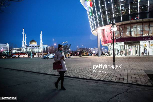 A pedestrian walks past the Asia Park mall near the NurAstana Mosque at night in Astana Kazakhstan on Saturday April 14 2018 Kazakhstan's gross...
