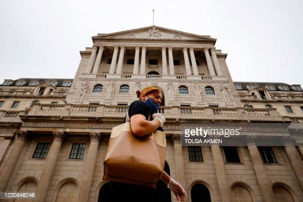 Pedestrian walks past the Bank of England in London on June 17, 2020. - The Bank of England, confronted by Britain's collapsing coronavirus-ravaged...