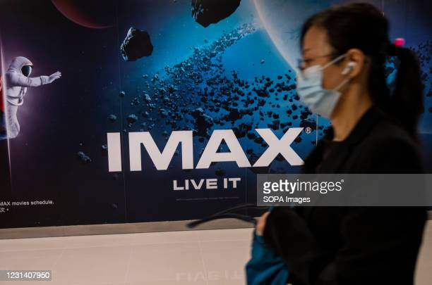 Pedestrian walks past the Canadian high-resolution film formats and projectors theatre company, Imax in Hong Kong.