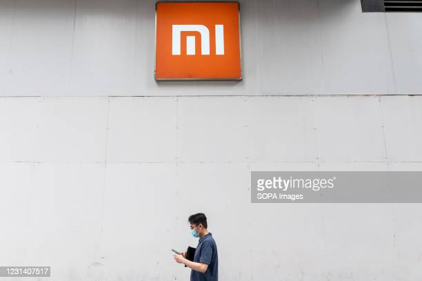 Pedestrian walks past the Chinese multinational technology and electronics brand Xiaomi flagship store and logo in Hong Kong.