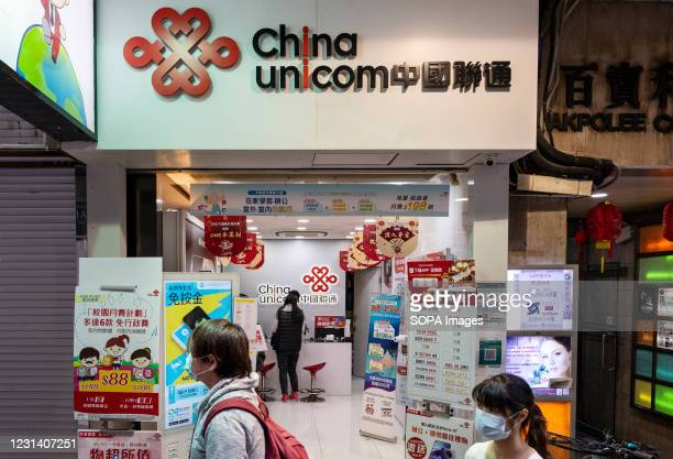 Pedestrian walks past the Chinese state-owned telecommunication corporation, China Unicom branch seen in Hong Kong.