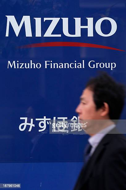 A pedestrian walks past the corporate logo of Mizuho Financial Group Inc displayed outside a Mizuho Bank Ltd branch in Tokyo Japan on Thursday Nov 14...