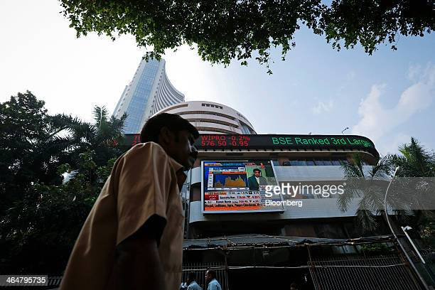 A pedestrian walks past the electronic ticker board that indicates stock figures at the Bombay Stock Exchange in Mumbai India on Thursday Jan 23 2014...