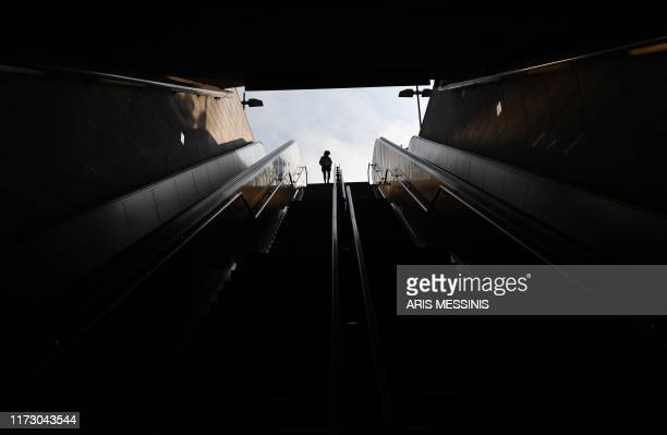 TOPSHOT A pedestrian walks past the entrance to a metro station in Athens on October 2 during a strike action against proposed government changes in...