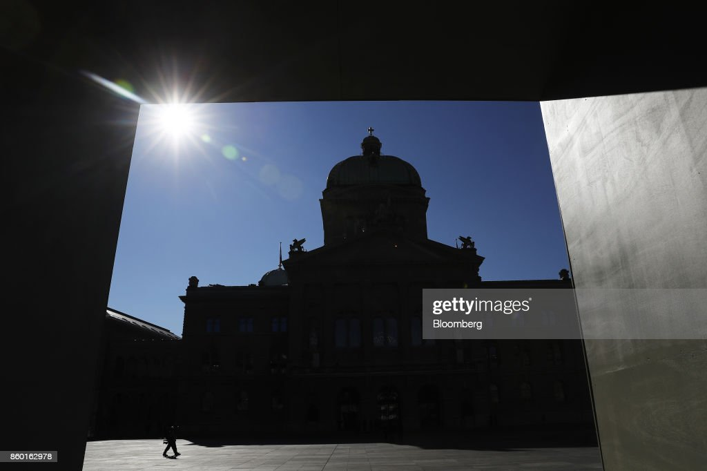A pedestrian walks past the Federal Palace, Switzerland's parliament building, in Bern, Switzerland, on Wednesday, Oct. 11, 2017. Big banks are pushing back against Swiss plans to relax rules that are making it hard for small financial firms to compete against the likes of UBS Group AGand Credit Suisse Group AG. Photographer: Stefan Wermuth/Bloomberg via Getty Images