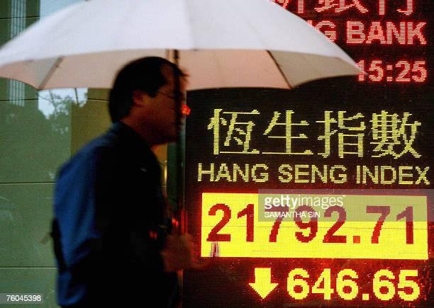 A pedestrian walks past the Hang Seng index board in Hong Kong 10 August 2007 Hong ong Kong share prices closed sharply lower 10 August down 288...