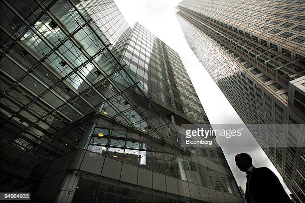 A pedestrian walks past the headquarters of the Financial Services Authority in the Canary Wharf financial district in London UK on Wednesday July 8...