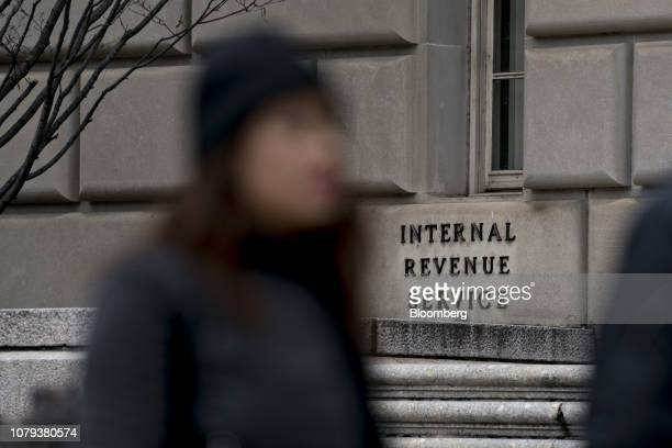 A pedestrian walks past the Internal Revenue Service headquarters in Washington DC US on Tuesday Jan 8 2019 The IRS will issue refunds to taxpayers...