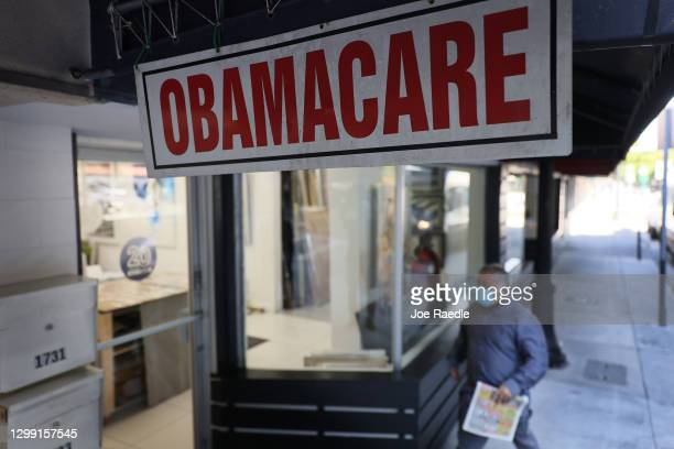 Pedestrian walks past the Leading Insurance Agency, which offers plans under the Affordable Care Act on January 28, 2021 in Miami, Florida. President...