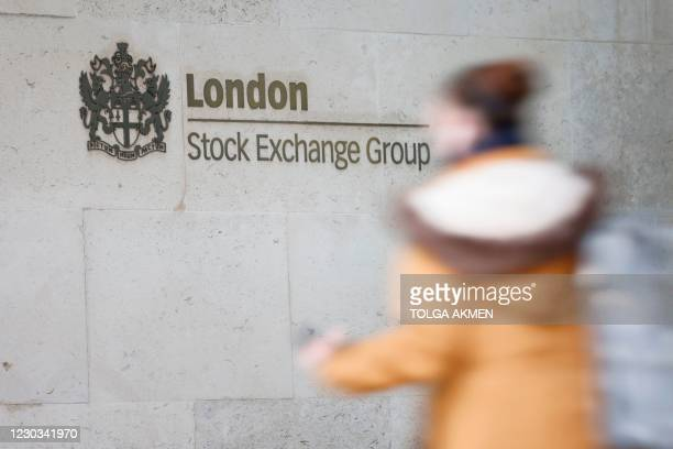 Pedestrian walks past the logo for the London Stock Exchange Group outside the stock exchange in London on December 29, 2020. - The London stock...