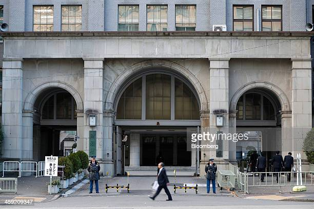 Pedestrian walks past the Ministry of Finance building as security officers stand guard in Tokyo, Japan, on Tuesday, Dec. 24, 2013. Japan unveiled a...