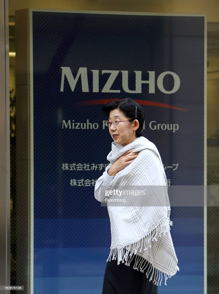 A pedestrian walks past the Mizuho Financial Group Inc. headquarters in Tokyo, Japan, on Tuesday, Feb. 26, 2013. Mizuho Financial Group Inc., Japan's third-biggest bank by market value, plans to cut an additional 600 jobs as it targets profit of 550 billion yen ($6 billion) in three years following the merger of its lending units. Photographer: Tomohiro Ohsumi/Bloomberg via Getty Images