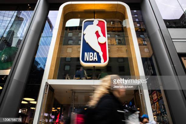 A pedestrian walks past the NBA store on 5th Avenue on March 12 2020 in New York City The National Basketball Association said they would suspend all...