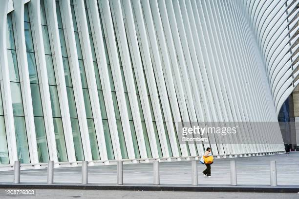 A pedestrian walks past the Oculus transportation hub in the Financial District of New York US on Monday March 30 2020 Roughly 37500 people have...