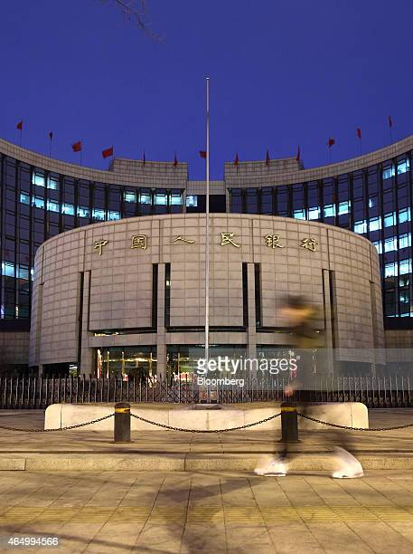 A pedestrian walks past the People's Bank Of China headquarters at night in the financial district of Beijing China on Monday March 2 2015 China's...
