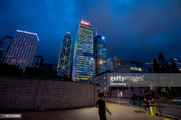 A pedestrian walks past the perimeter walls of the Chinese People's Liberation Army Forces Hong Kong Building as the Bank of America Tower second...