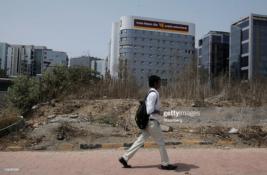 A pedestrian walks past the Punjab National Bank Ltd building in Mumbai India on Wednesday April 25 2012 Savings in India rose 134 percent in the...