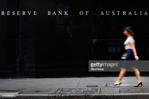 A pedestrian walks past the Reserve Bank of Australia headquarters in the central business district of Sydney Australia on Tuesday March 4 2014...