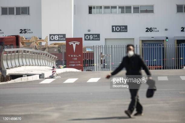 A pedestrian walks past the Tesla Inc Gigafactory in Shanghai China on Monday Feb 17 2020 Tesla has fully resumed deliveries of its Chinabuilt model...