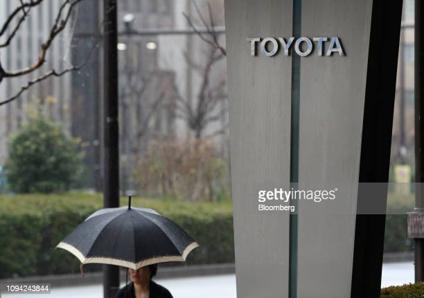 A pedestrian walks past the Toyota Motor Corp head office in Tokyo Japan on Wednesday Feb 6 2019 Toyota cut its fullyear netincome forecast after a...