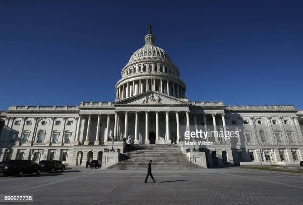 A pedestrian walks past the US Capitol as congressional lawmakers work on a deal to fund the government and avert a shutdown by midnight Friday on...