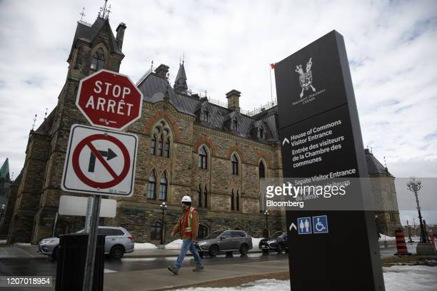 A pedestrian walks past the West Block building of Parliament Hill the temporary home to the House of Commons in Ottawa Ontario Canada on Friday...