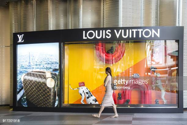 A pedestrian walks past the window display of a Louis Vuitton store operated by LVMH Moet Hennessy Louis Vuitton SE in the Ion Orchard mall jointly...