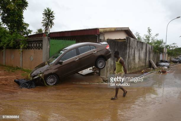 TOPSHOT A pedestrian walks past the wreckage of a vehicle on a street in Abidjan on June 19 after floodwaters receded following an overnight downpour...