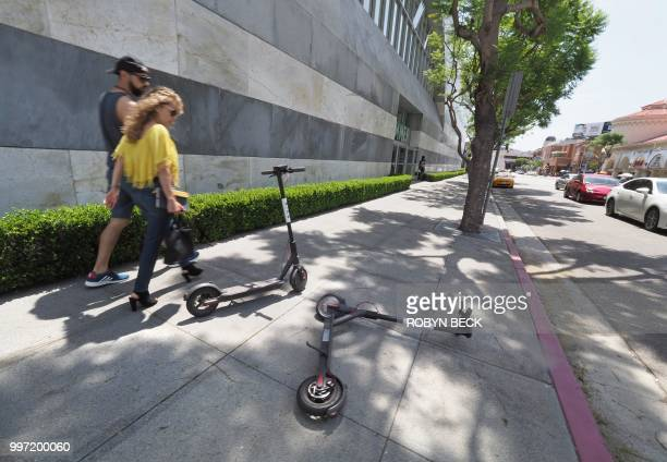 A pedestrian walks past two Bird dockless scooters one laying on its side in the middle of a sidewalk in the Westwood section of Los Angeles...