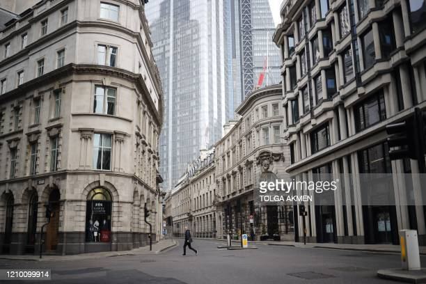 A pedestrian walks the neardeserted streets of the City of london on April 16 during the novel coronavirus Covid19 pandemic The British government on...
