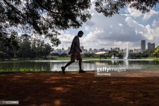 Pedestrian walks through a park near luxury apartment buildings in the Vila Nova Conceicao neighborhood of Sao Paulo, on Monday, May 6, 2019. The...