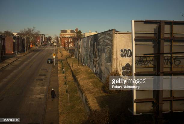 A pedestrian walks through a partly abandoned neighborhood January 9 2018 in Baltimore Maryland Often named one of the country's most dangerous big...