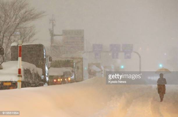 Pedestrian walks through heavy snow in Fukui, Japan, on Feb. 7 alongside Route 8 where trucks are stranded, as snowfall continues to hit the Sea of...