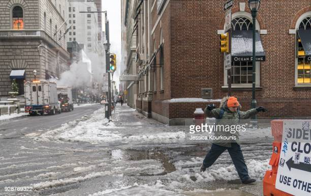 A pedestrian walks through snow on March 7 2018 in Philadelphia Pennsylvania This is the second nor'easter to hit the Northeast within a week and is...