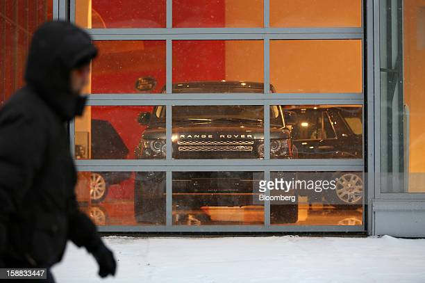 A pedestrian walks through snow past a Range Rover automobile on display in the window of a Jaguar Land Rover auto dealership in Moscow Russia on...