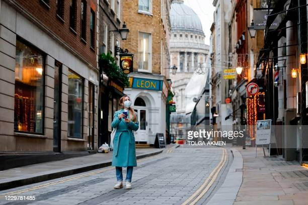 Pedestrian walks through the near-deserted streets of the City of London in London on November 25, 2020. - Britain's economy is set to shrink 11.3...