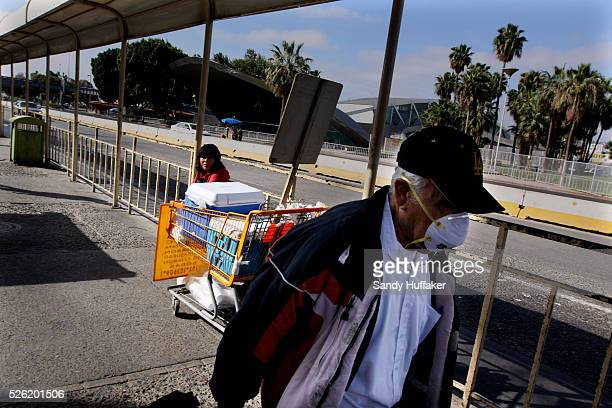 A pedestrian walks towards the MexicoUnited States border crossing wearing a surgical mask near the Port of entry on Sunday May 3 2009 The H1N1 Swine...