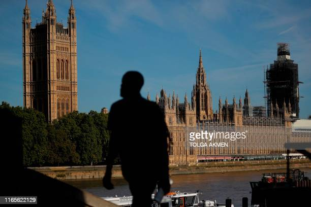 A pedestrian walks up a staircase on the southern bank of the River Thames with Houses of Parliament seen in the background in London on September 2...