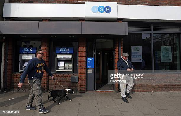 A pedestrian walks with a dog as he passes a customer leaving a TSB bank branch operated by TSB Banking Group Plc in London UK on Friday March 13...