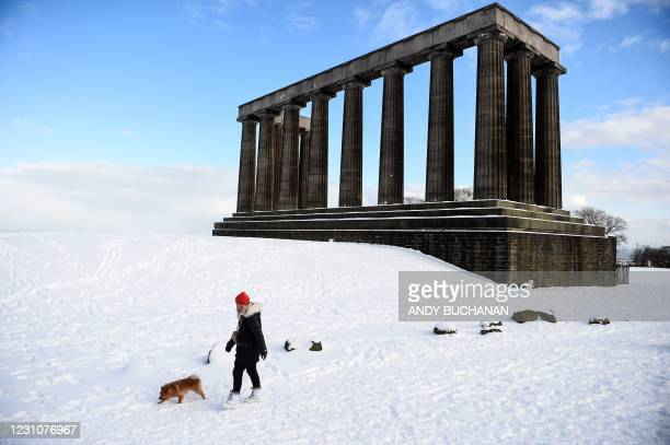Pedestrian walks with a dog past the National Monument on the snow covered Calton Hill in the centre of Edinburgh on February 10, 2021. - Cold...