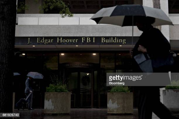 A pedestrian walks with an umbrella past the Federal Bureau of Investigation headquarters in Washington DC US on Thursday May 11 2017 President...