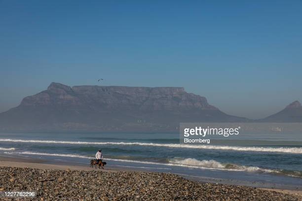 A pedestrian walks with dogs at Sunset Beach as Table mountain stands beyond in the Milnerton district of Cape Town South Africa on Thursday July 23...