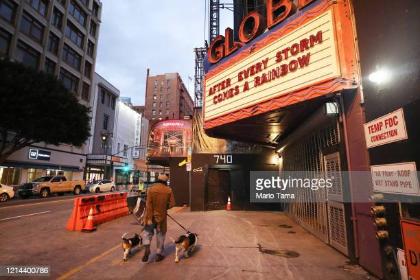 A pedestrian walks with two dogs past the shuttered Globe Theatre with the message 'After Every Storm Comes a Rainbow' written on the marquee as the...