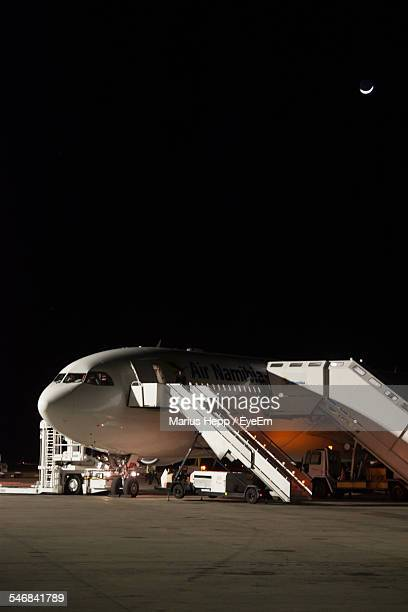 Pedestrian Walkway Connected To Airplane At Night