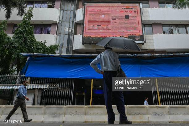 Pedestrian watches share prices on a digital broadcast as he stands outside the Bombay Stock Exchange in Mumbai on August 4, 2021.