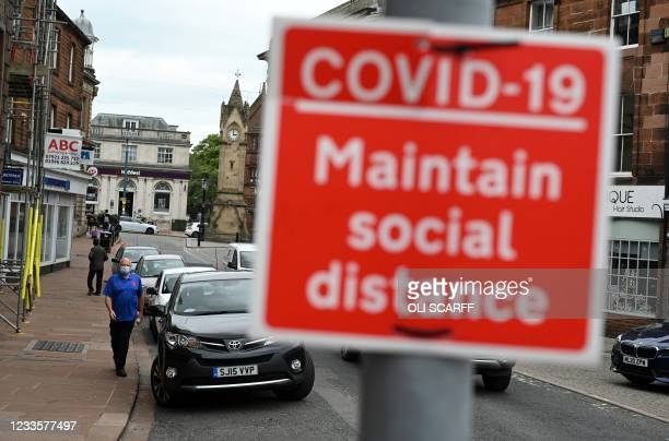 Pedestrian wearing a face covering due to Covid-19, walks near a 'social distancing' sign in Penrith in Cumbria, north west England on June 21...
