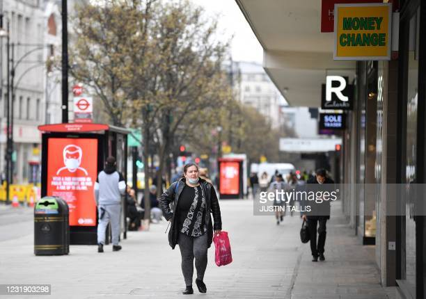 Pedestrian wearing a face covering due to Covid-19, walks past closed shops on a quiet Oxford Street in central London on March 24, 2021. - Britain's...