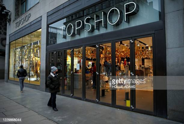 Pedestrian wearing a face covering due to the COVID-19 pandemic, walks past a temporarily closed-down Topshop clothes store, operated by Arcadia, in...
