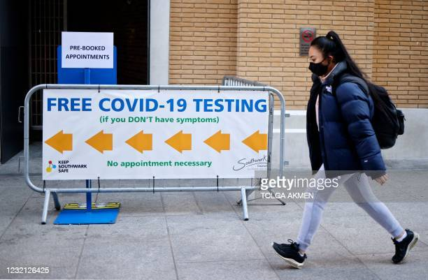 Pedestrian wearing a face covering walks past a sign directing people to a rapid lateral flow Covid-19 testing centre at London Bridge train station...